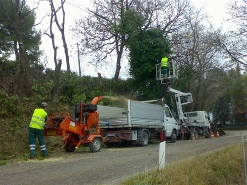 Operai con macchinari pulendo i lati della strada