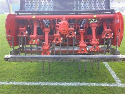 Macchina raggruppando l'erba di un campo di calcio