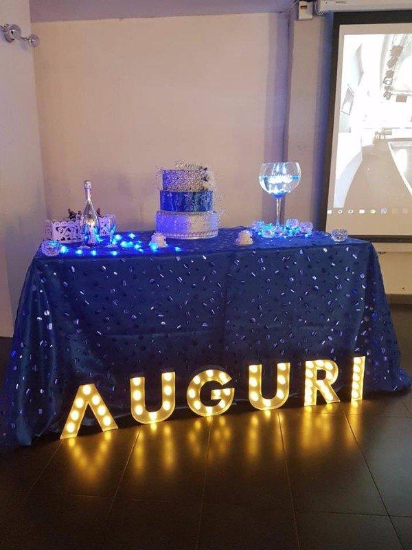 n tavolo con una tovaglia blu,sopra una torta e una scritta di Auguri luminosi