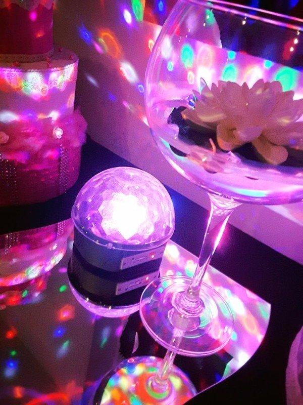 un bicchiere con dentro un fiore e una pallina luminosa