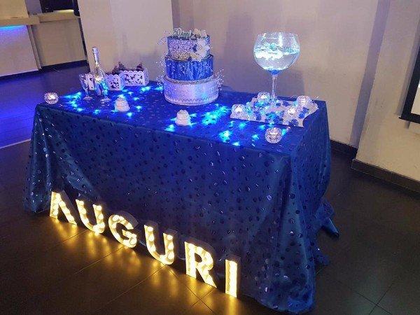 un tavolo con una tovaglia blu,sopra una torta e una scritta di Auguri luminosi