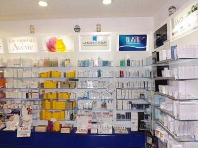 bancone blu e dietro delle mensole con dei medicinali esposti