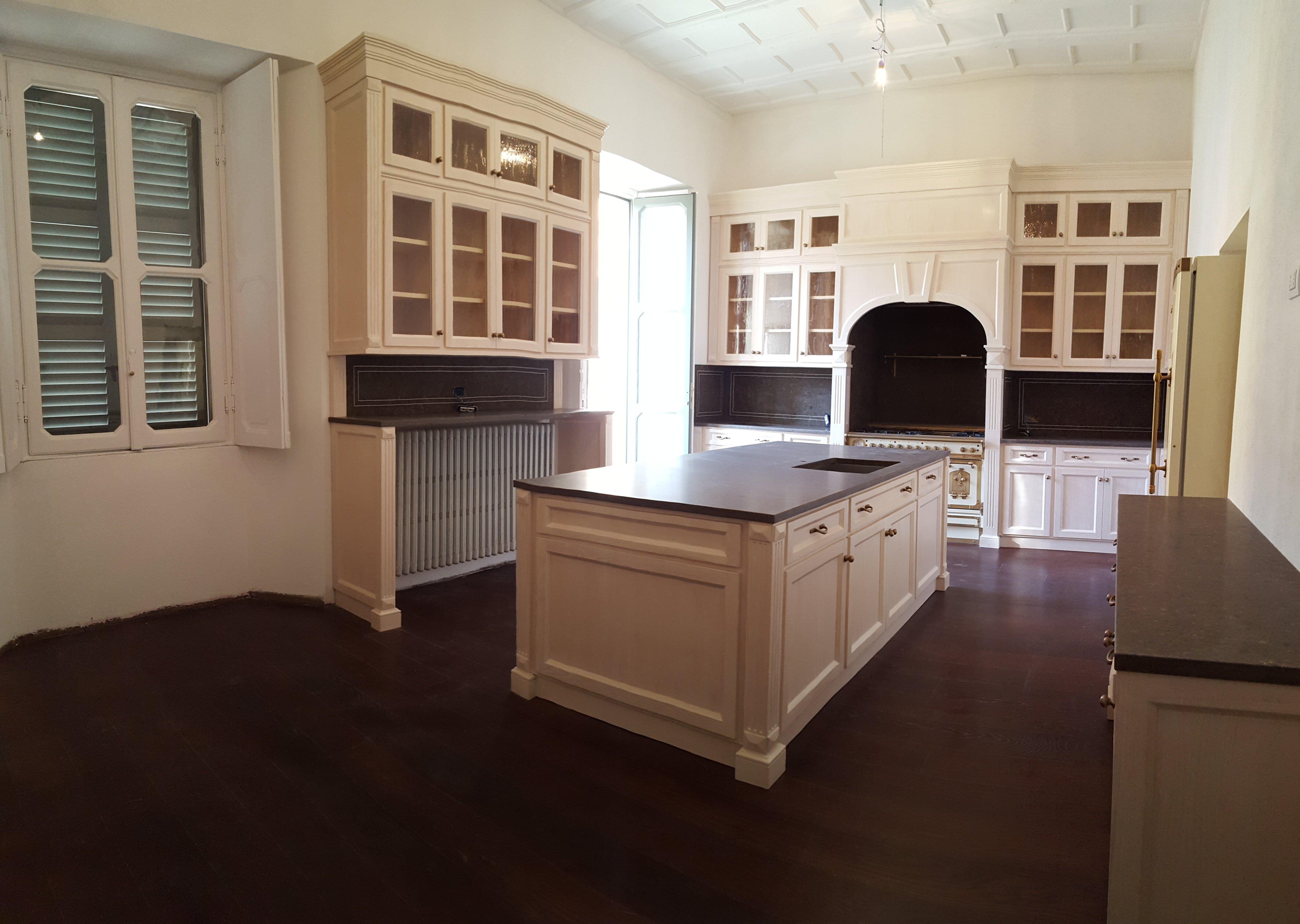 cucina con pavimento scuro e mobili chiari