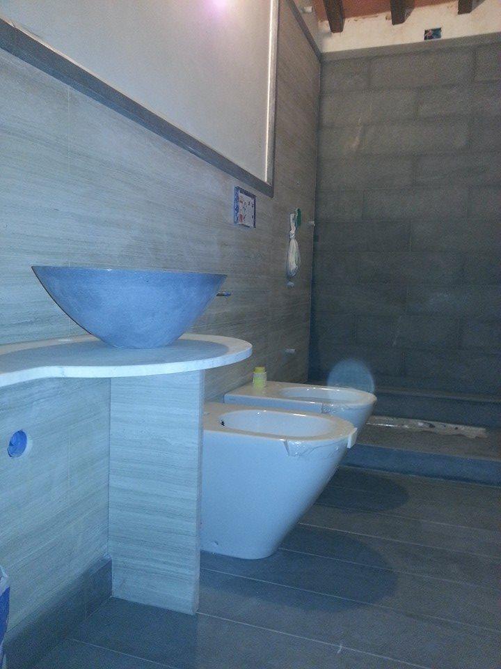 bagno con muri grigi stile pietre