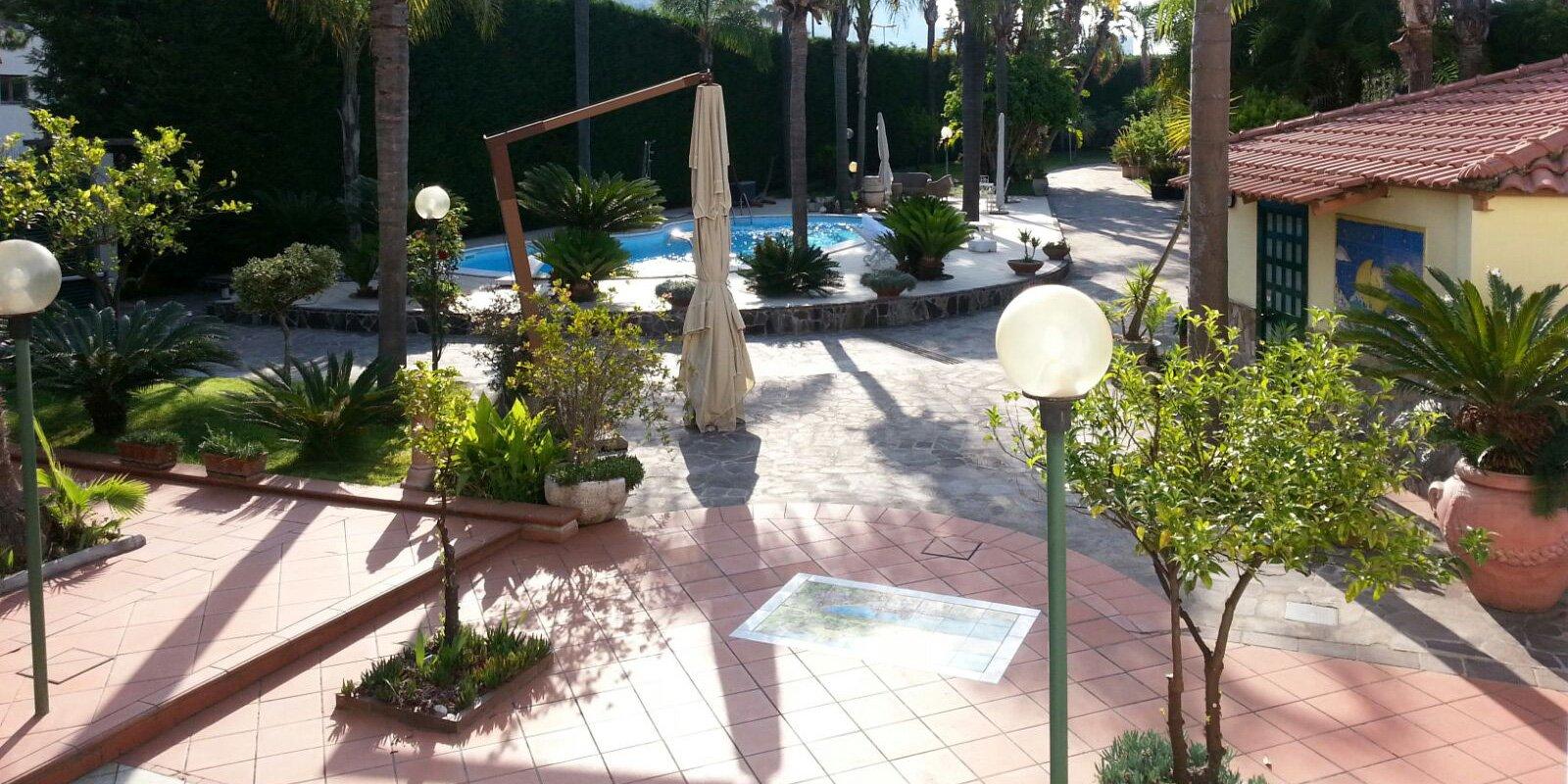 Cortile della villa, vista di piscina, palme piccole e grandi. Ombrellone da giardino con asta in legno pieghevole e lampioni