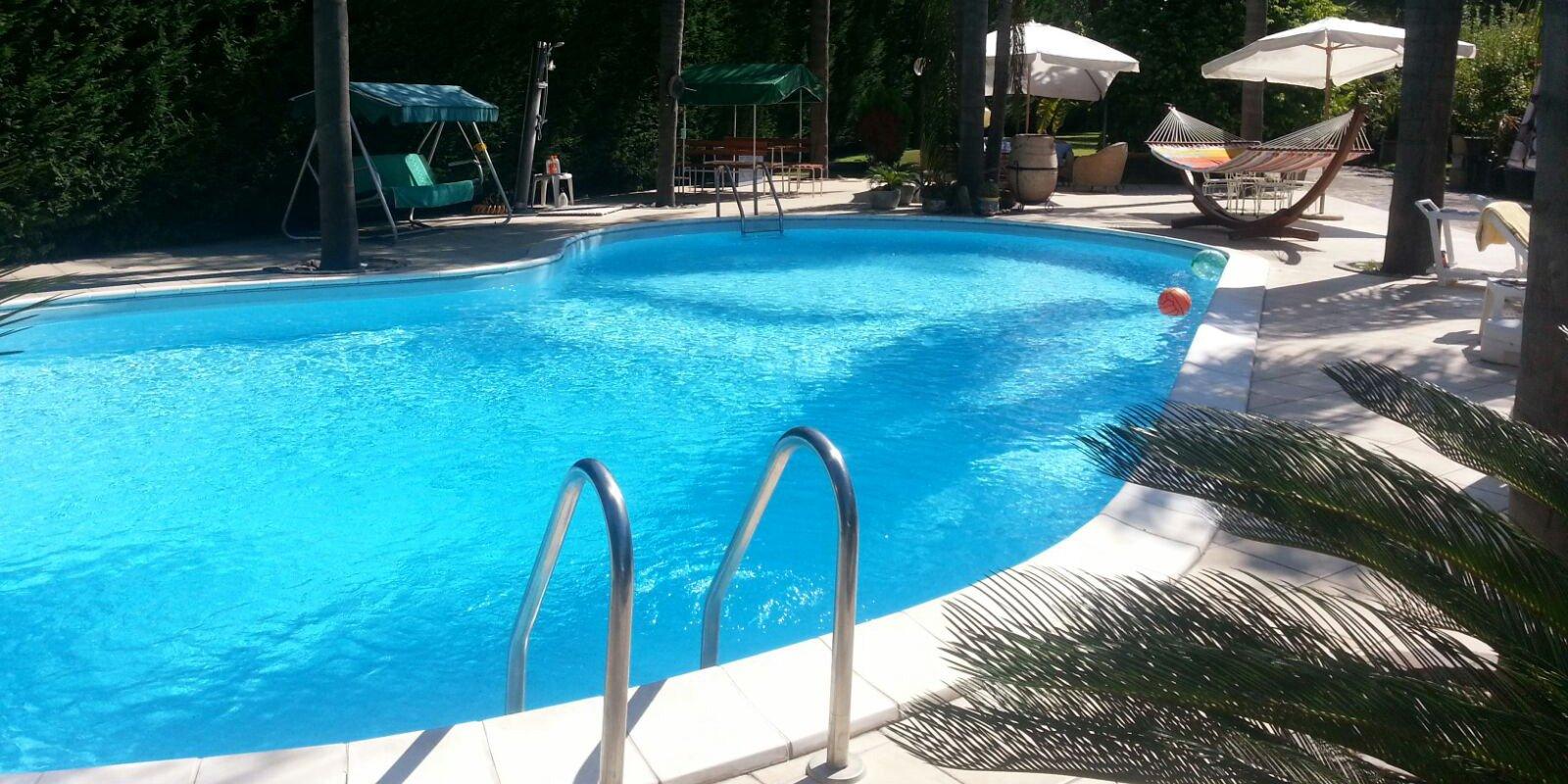 vista dalla piscina con ombrelloni, amaca, tendalini e due palloni che galleggiano in acqua