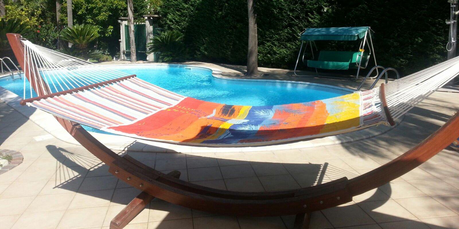 Amaca su struttura in legno a bordo piscina con tessuto multicolore