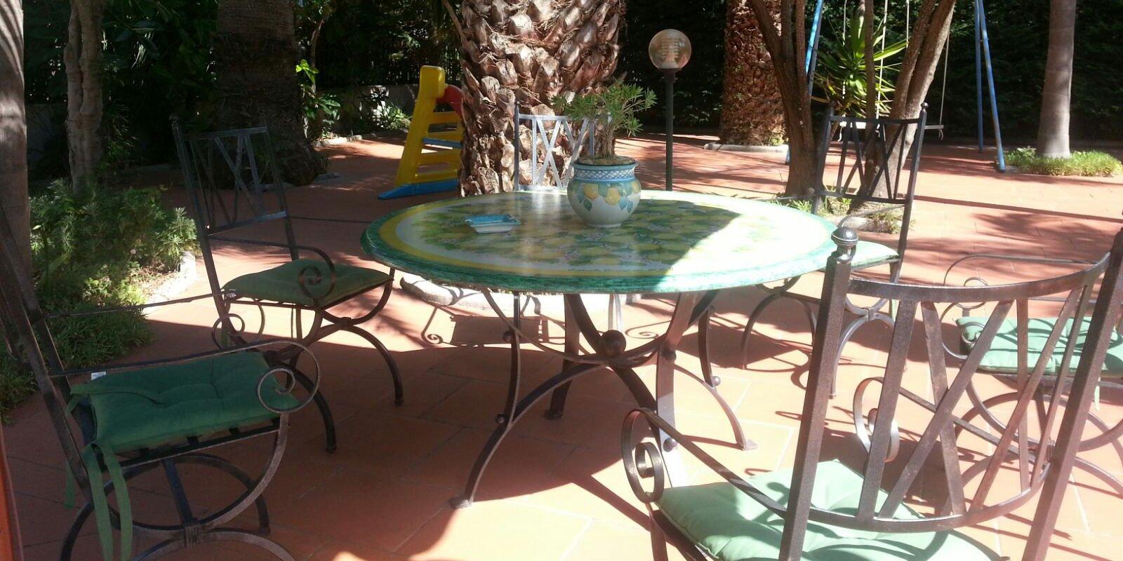 giardino con delle palme, tavolino rotondo, sedie in ferro battuto scivolo e altalena per bambini