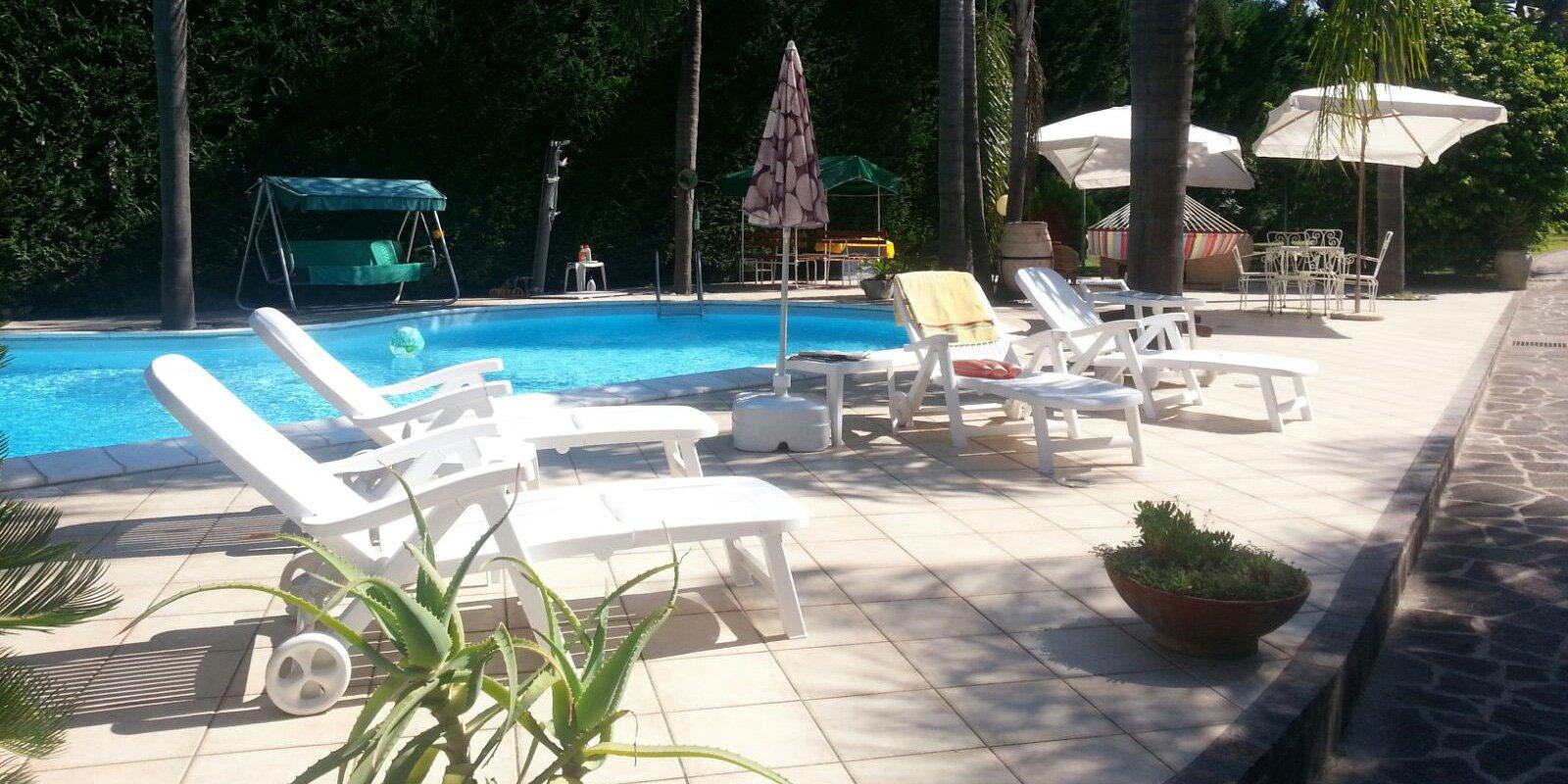 piscina con sdraio con rotelle dondolo con tendalino verde e ombrelloni