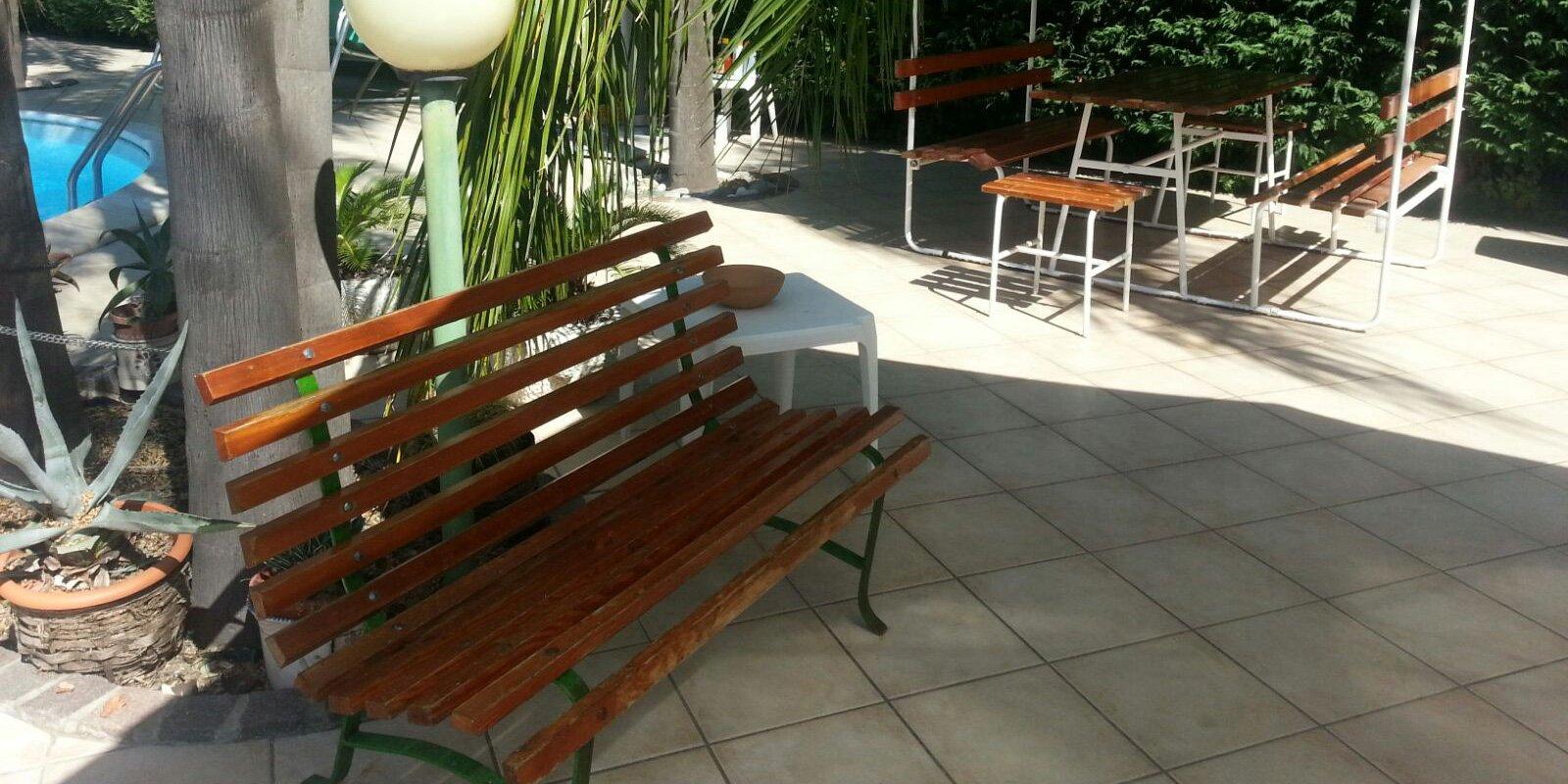 giardino con  palme, panchine in legno, lampioncini e tendalino verde