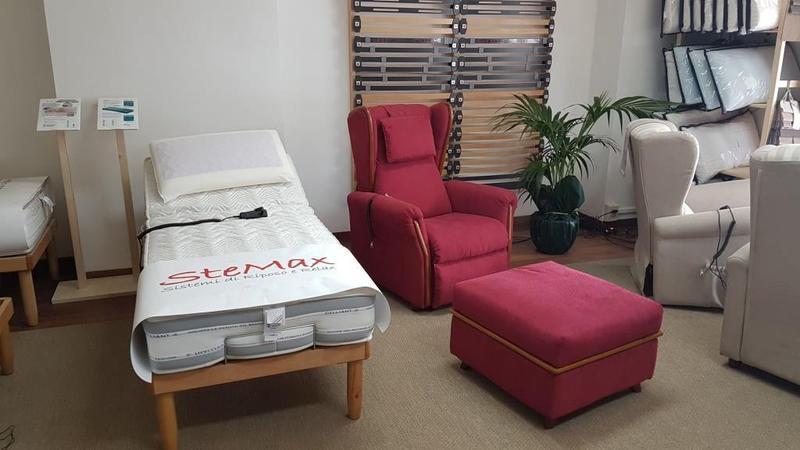 un letto matrimoniale una poltrona rossa e un poggia piedi