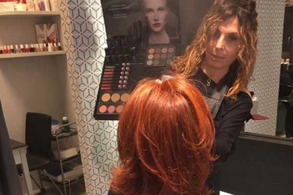 una donna con capelli rossi seduta in un salone di parrucchieri e in piedi una parrucchiera che sta per iniziare il lavoro a Imola