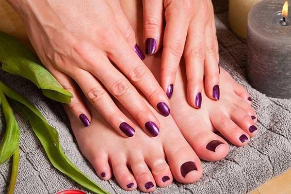 visuale di mani e piedi con uno smalto viola e accanto una candela a Imola