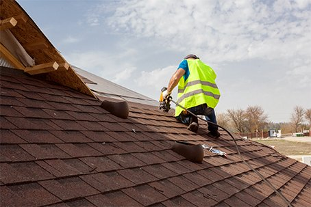 Construction worker putting the asphalt roofing on a home in Wisconsin Rapids