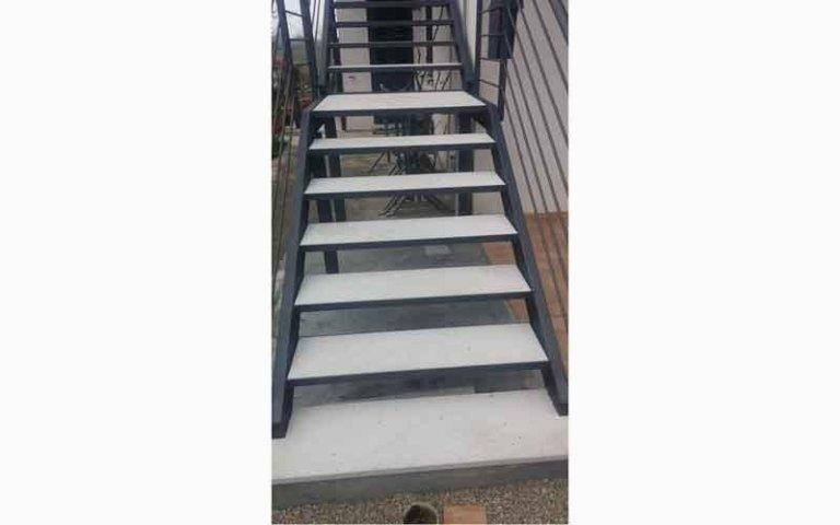delle scale da esterno con dei corrimani in ferro