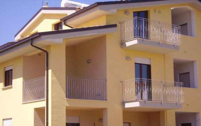 facciata di una casa con dei balconi e ringhiere in ferro