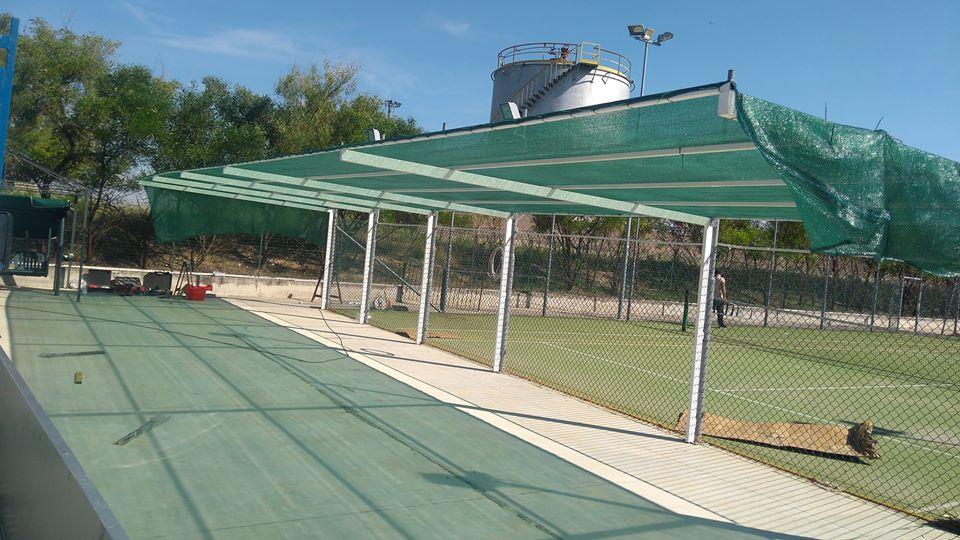 un campo da tennis con recinzione in metallo a rete