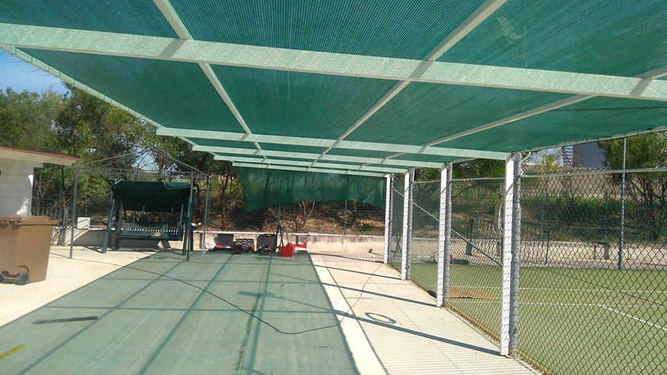 una copertura con un telo verde vicino a un campo da tennis