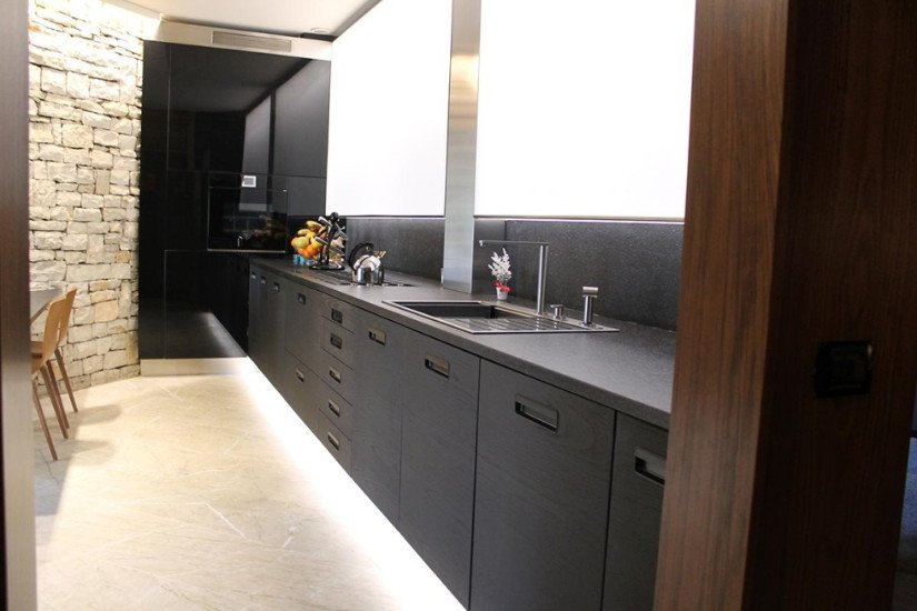 una cucina con mobili color grigio scuro