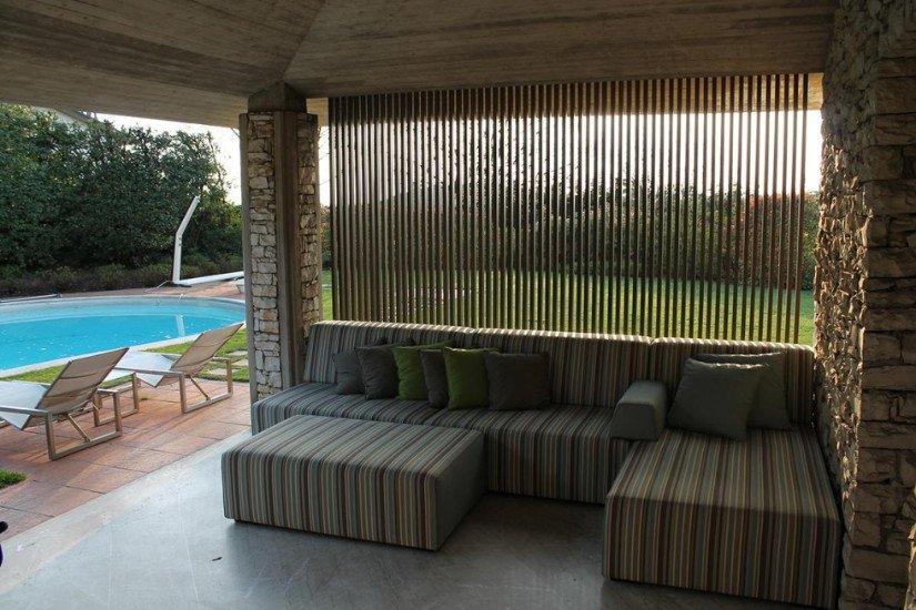 un divano azzurro angolare e visto di una piscina all''esterno