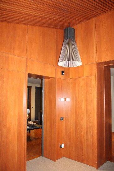 delle pareti ricoperte in legno e una lampada sospensione