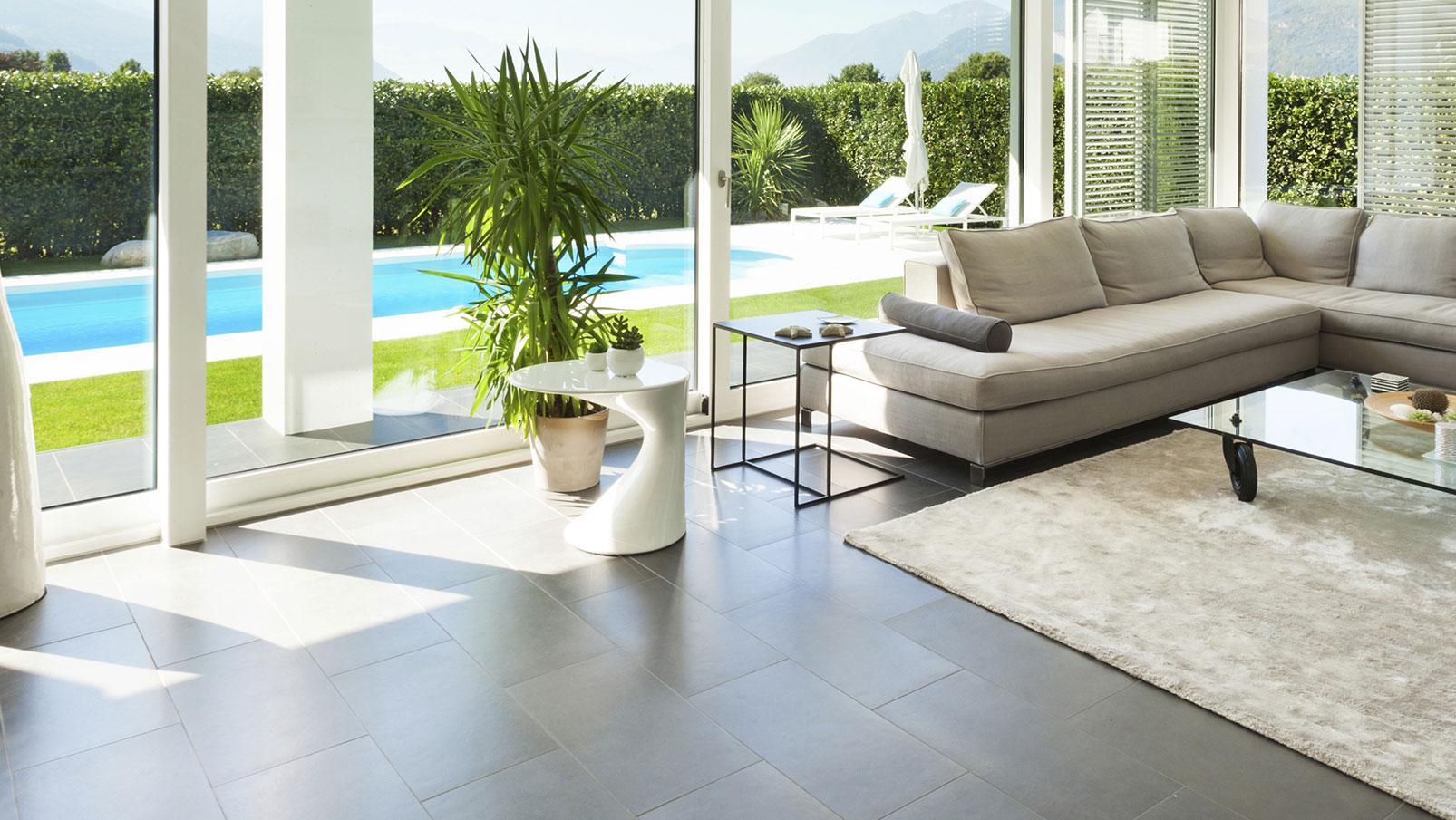 Grande salotto, sofà sotto forma di ele, tappeto grigio, tavola bassa di vetro con ruote, tavola bassa di PVC bianco, grandi porte scorrevoli di PVC bianco
