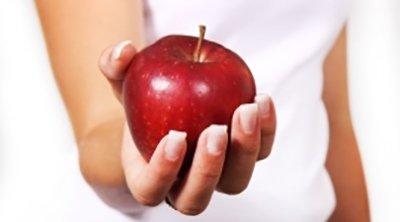 una mano di donna tiene una mela