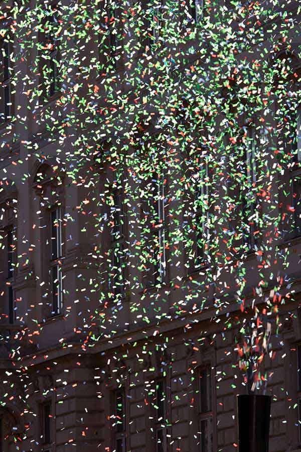 cannon shooting multi-coloured confetti into the street
