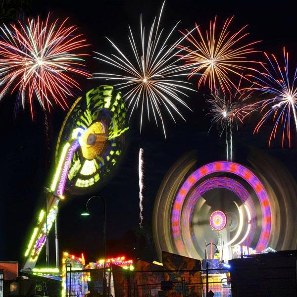 fireworks display over fair ground rides