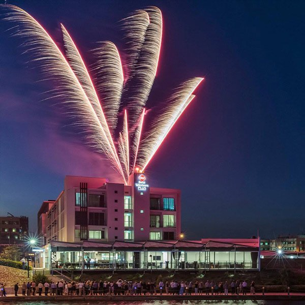 fireworks display on roof of modern building with spectators below