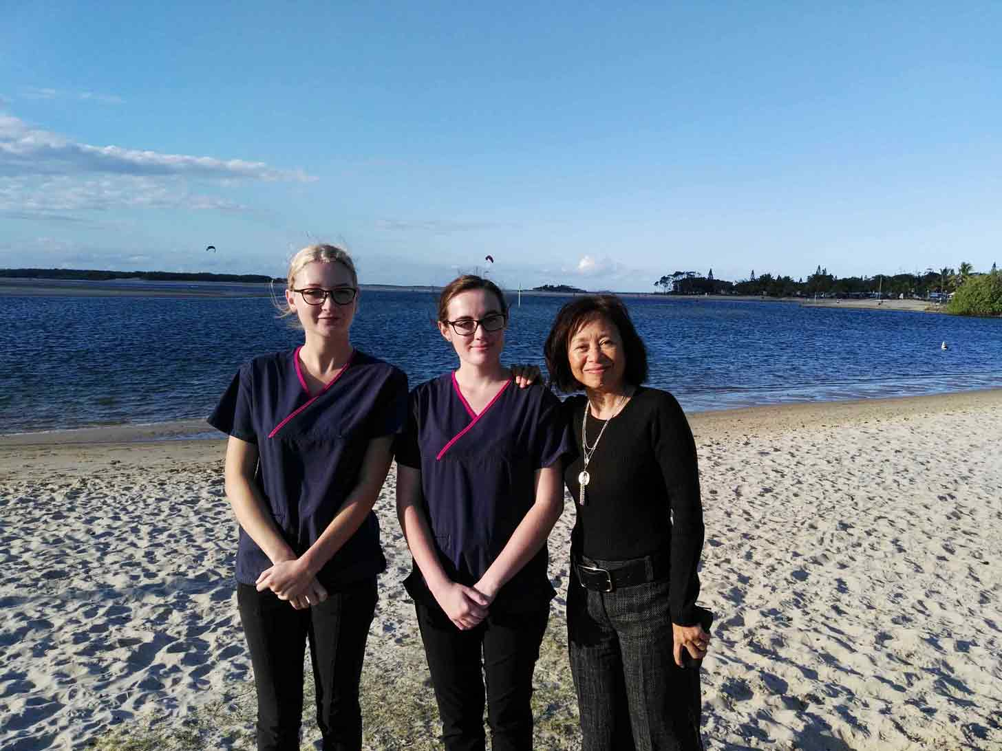 three girl employees standing by ocean