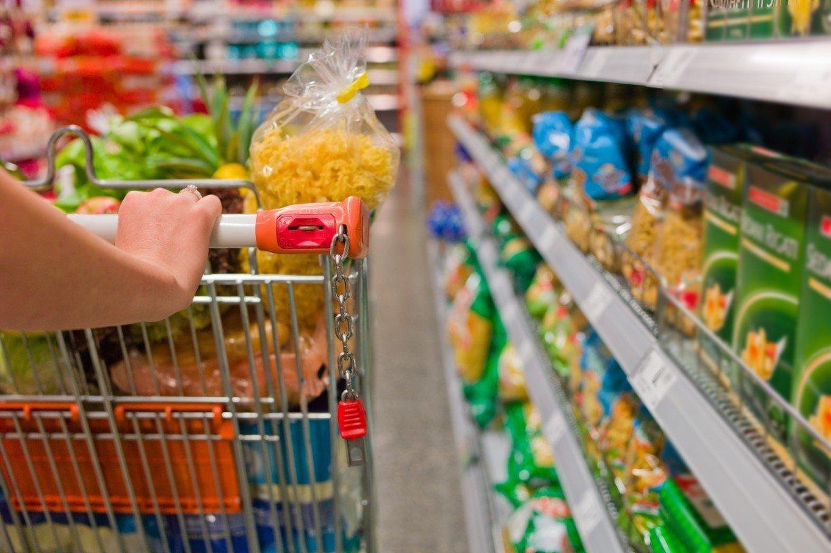 Donna spingendo il carrello della spesa pieno di vari prodotti