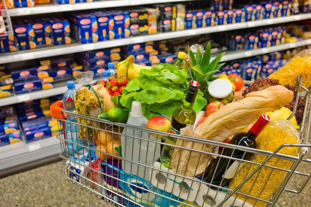 In il carrello della spesa va pasta,la verdura, la frutta,pane,vino,acqua e prodotti per la pulizia