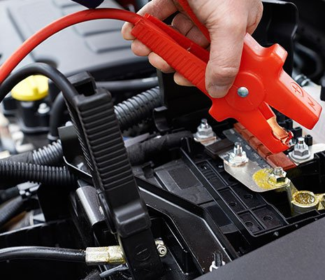 Alaska Auto Repair & Sales Inc mechanic attaching jumper cables to car battery