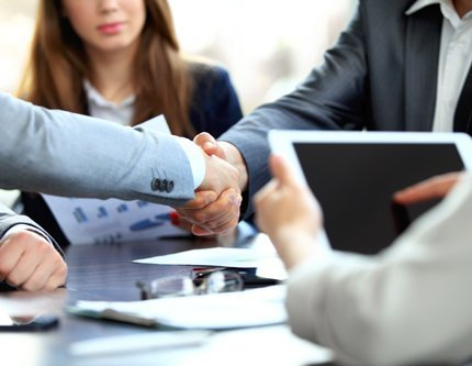 Professionals shaking hands after getting accounting assistance
