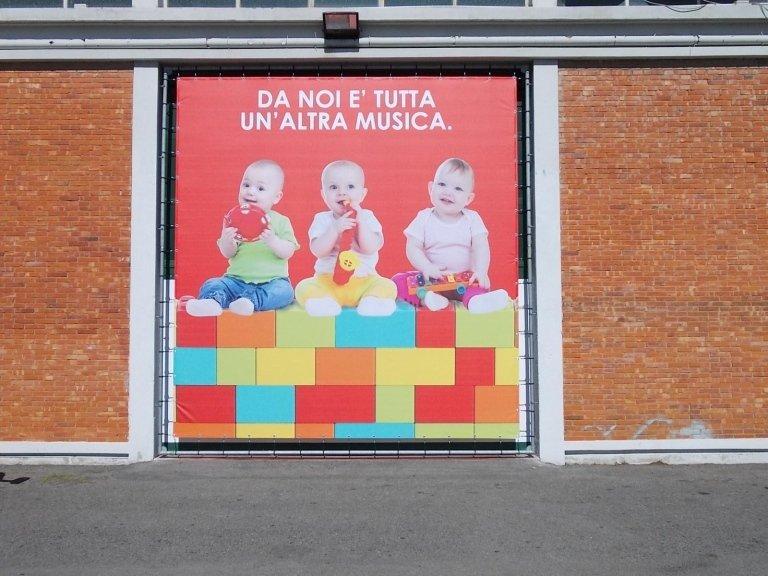 un cartello con scritto da noi è tutta un'altra musica e tre neonati con dei giochi