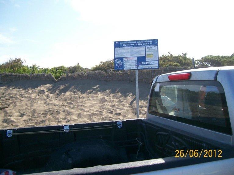 un pick-up e un cartello sulla spiaggia