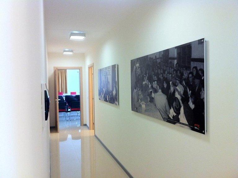 dei quadri con delle foto in bianco e nero sul muro di un corridoio