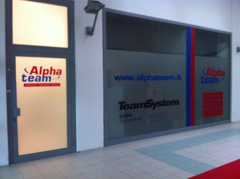 dei loghi pubblicitari su una vetrina con scritto Alpha team