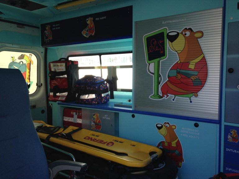 interno di un ambulanza con una barella e degli adesivi di un orso