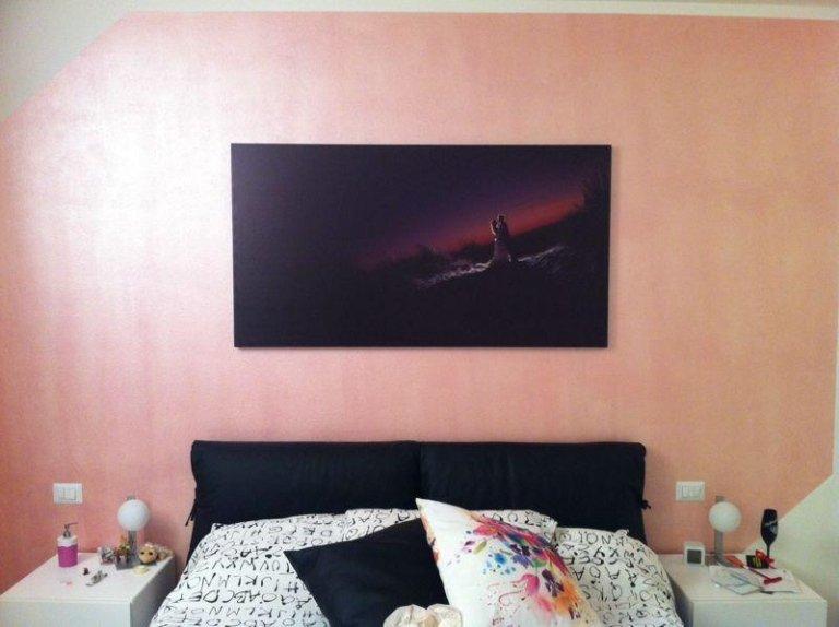 un letto e sopra un quadro a sfumature rosse e nere