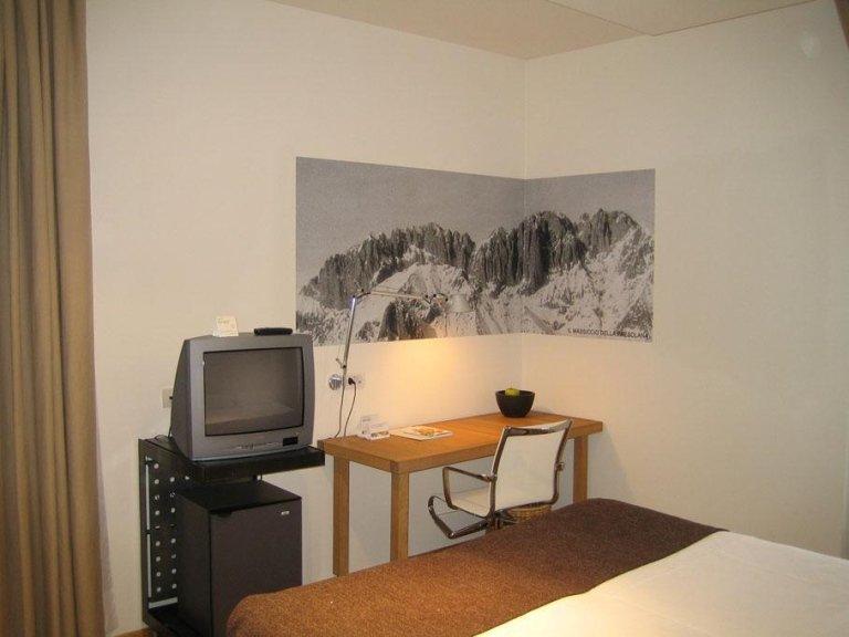 un poster raffigurante delle montagne in una stanza con TV e scrivania