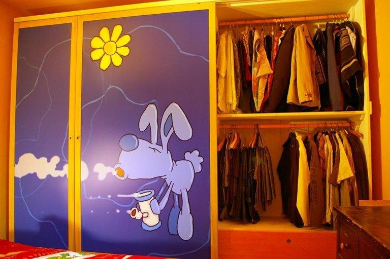 un armadio con ante in legno e l'immagine di un coniglio grigio e un fiore giallo