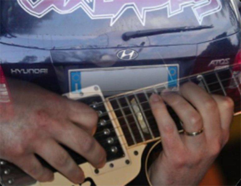 due mani che suonano una chitarra e una Hyundai Atos blu