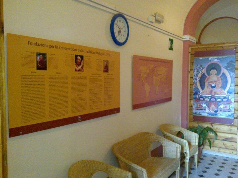 3 sedie in paglia e dei pannelli illustrativi con scritto Fondazione per la prevenzione della tradizione Mahayana