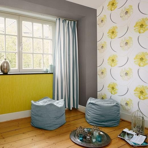 due pouf azzurri in una stanza con tappezzeria bianca a fiori gialli