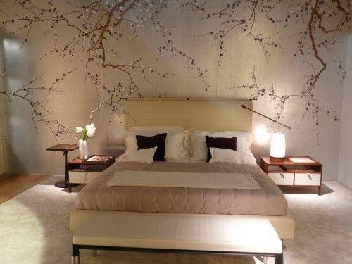 un letto matrimoniale e una parete con tappezzeria a disegni di rami e fiori
