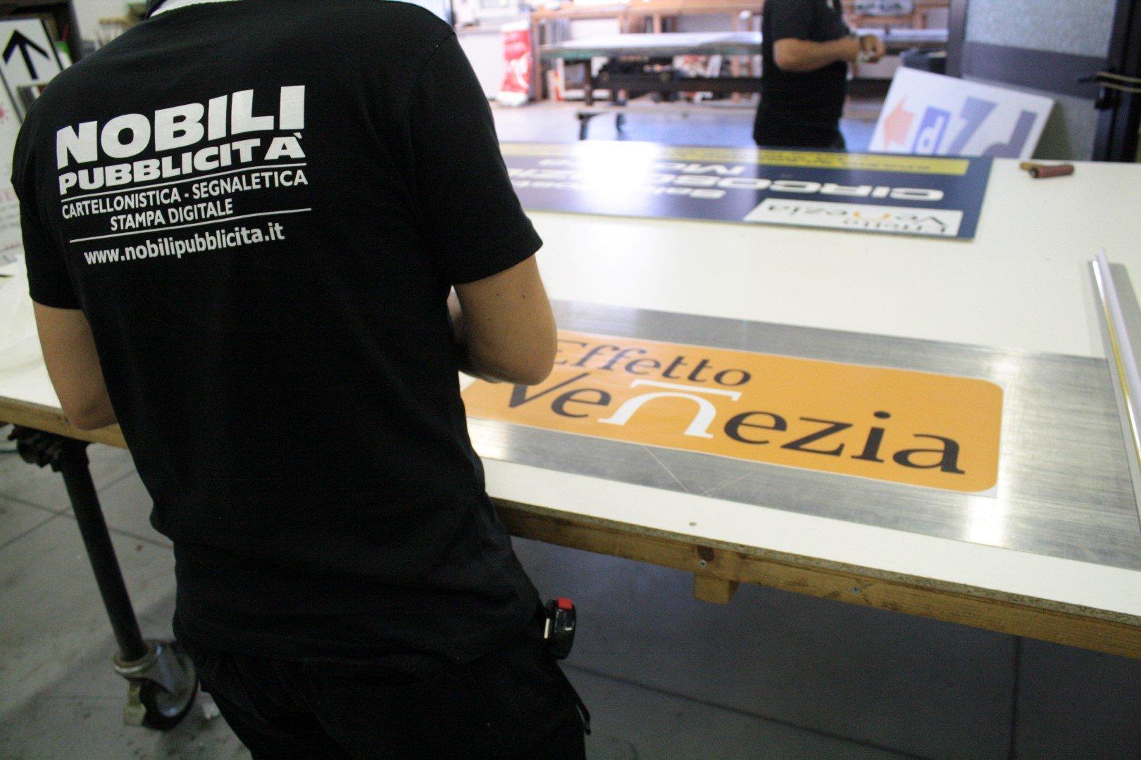 persona con maglietta NOBILI Pubblicita` che lavora un pannello con scritto EFFETTO VENEZIA