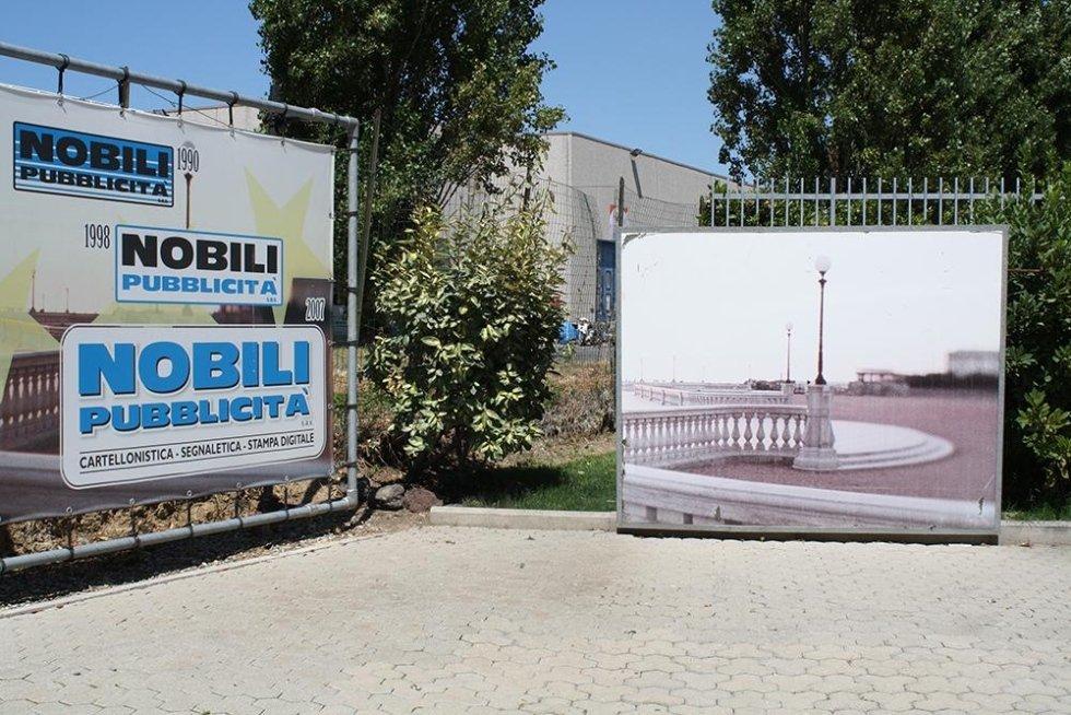 un cartello pubblicitario con scritto Nobili pubblicità e un altro cartello con l'immagine di una citta`