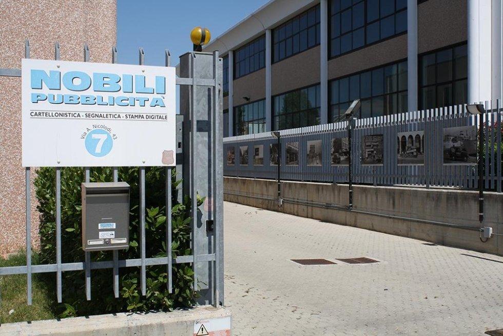 un cancello aperto e un cartello con scritto Nobili pubblicità